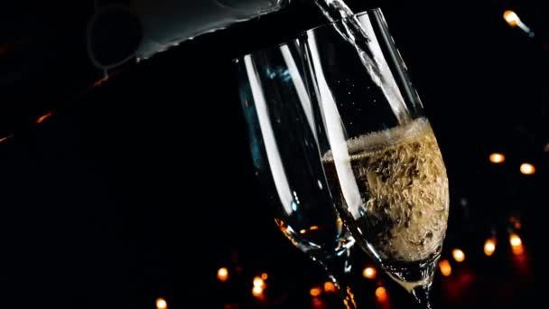 Barkeeper Gießen Champagner in Flöten mit goldenen Blasen auf schwarzen dunklen Hintergrund Licht