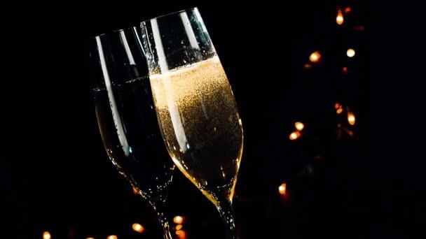 Champagner Flöten mit goldenen Blasen auf schwarzen dunklen Hintergrund Licht