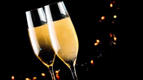 Barmann gießt Champagner in Flöten mit goldenen Blasen auf schwarzem, dunklem Hintergrund