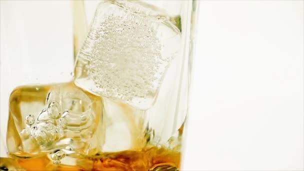 Close-up nalévání whisky na bílém pozadí