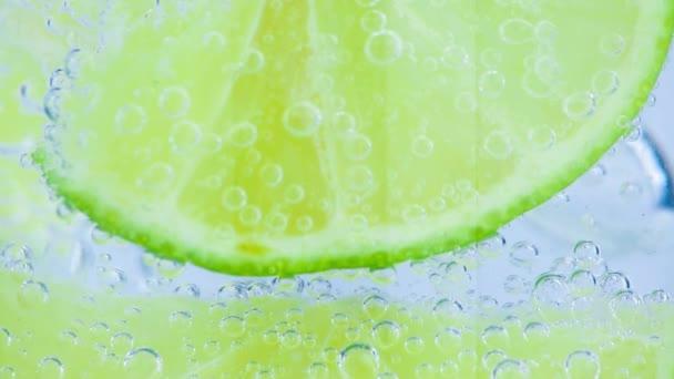 Šumivá voda s ledem a plátky vápna na bílém pozadí
