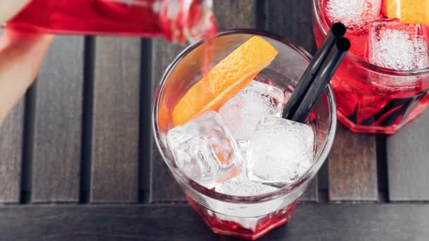 Top of view of pouring red spritz aperitif aperol cocktail with orange slices and ice cubes