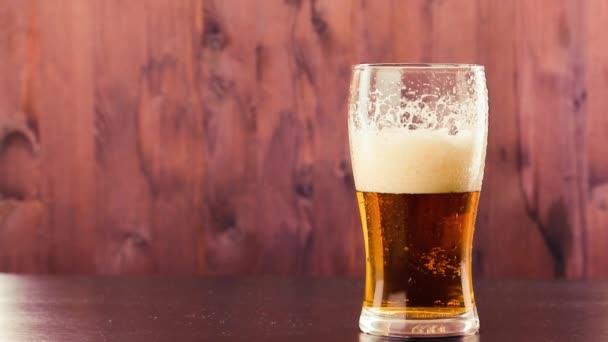 nalil pivo ve skle s bílou pěnou na dřevo
