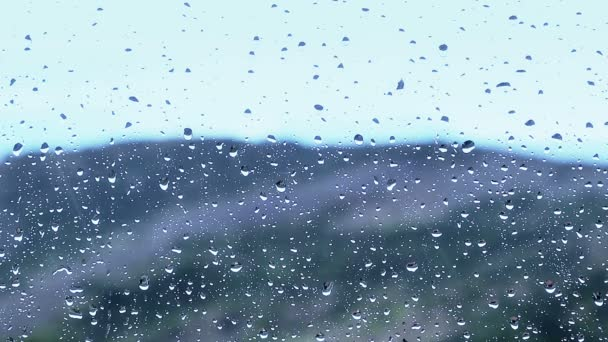 Close-up of water droplets movement on glass with mountain view blur and rain in background