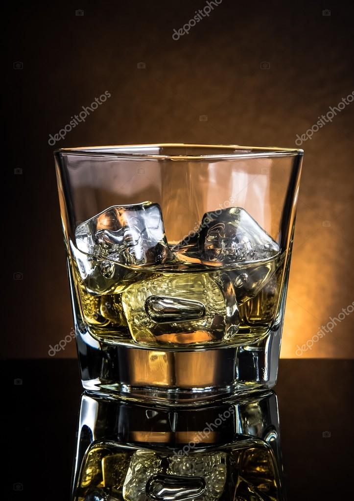 Glass Of Whiskey On Black Table With Reflection Warm Atmosphere