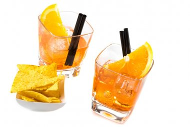 top of view of two glasses of spritz aperitif aperol cocktail with orange slices and ice cubes near tacos chips