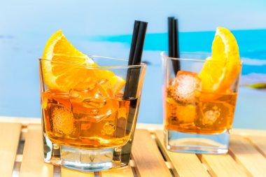two glasses of spritz aperitif aperol cocktail with orange slices and ice cubes on blur beach background