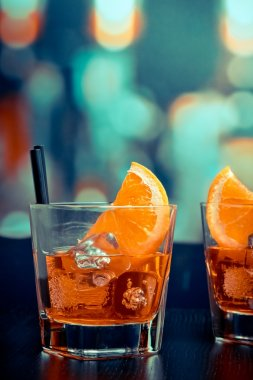 glasses of spritz aperitif aperol cocktail with orange slices and ice cubes on bar table, pop style atmosphere background