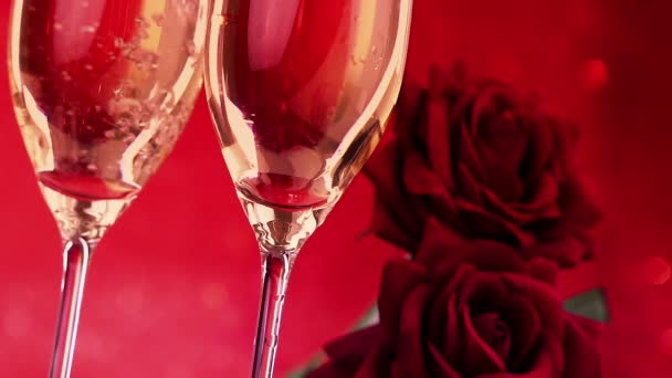 pouring champagne flutes with bubbles near red roses on red bokeh background, love and valentine day