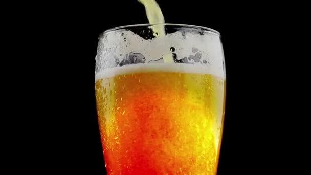 nalil pivo s pěnou do skla na černém pozadí