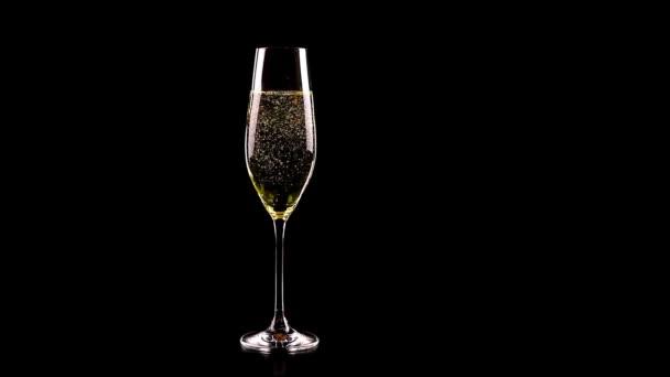 Mann gießt Champagner auf schwarzen Tisch vor schwarzem Hintergrund, nicht trinken und fahren, betrunken und am Steuer
