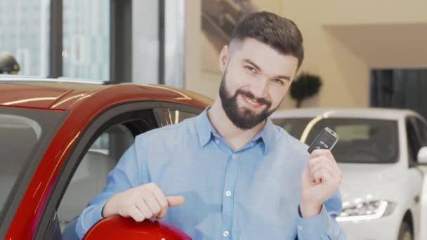 Happy attractive man showing car keys to the camera at dealership salon