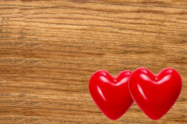Two red hearts on wooden texture close-up background