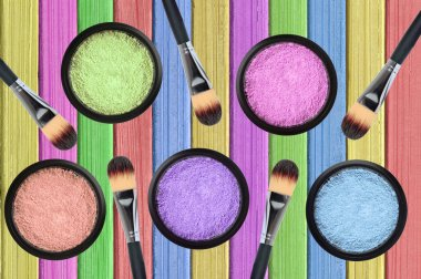 set of many eyeshadows and brushes on painted color wooden textu