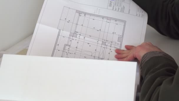 Nahaufnahme eines selbstbewussten Architekten in Freizeitkleidung, der mit architektonischem Plan arbeitet