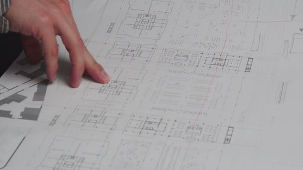 Großaufnahme eines männlichen Konstrukteurs sitzt am Schreibtisch im Büro, Baupläne liegen auf seinem Schreibtisch
