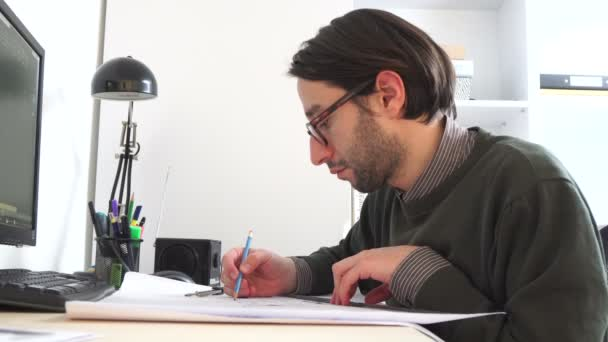 Young architect male In casual wear working in office on desk, types on a laptop, blueprints laying on her desk