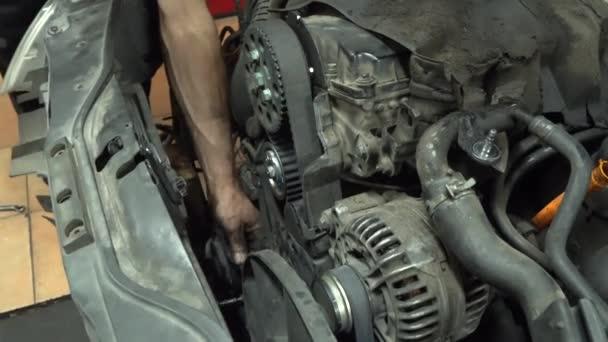 Autószerelő gumi övet cserél. Automatikus szervizelés vezérlése