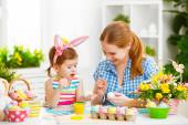 Fotografie happy family mother and child girl paints eggs for Easter