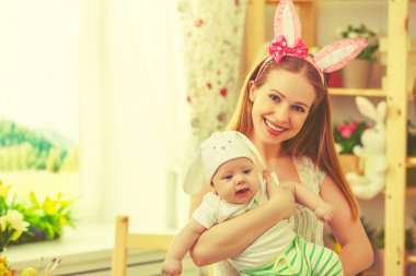 happy family celebrating easter mother and baby with bunny ears