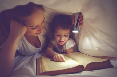 Family reading bedtime. Mom and child reading book with a flashl