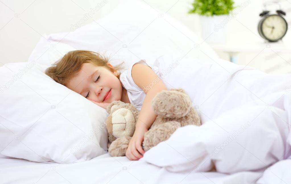 kind m dchen schl ft im bett mit teddyb r stockfoto. Black Bedroom Furniture Sets. Home Design Ideas