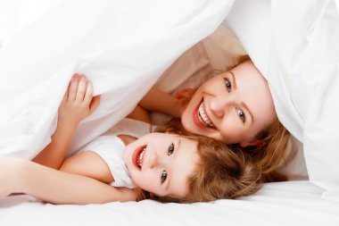 Happy family mother and child playing and laughing in bed