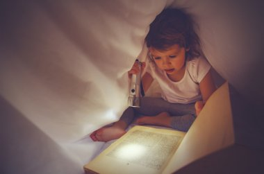 child girl reading  book in dark, under covers in bed with light