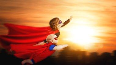 children superheroes flying across sunset sky