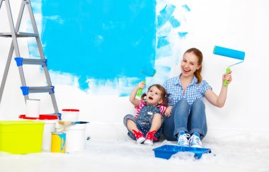 Happy family mother and child daughter making repairs, paint wal