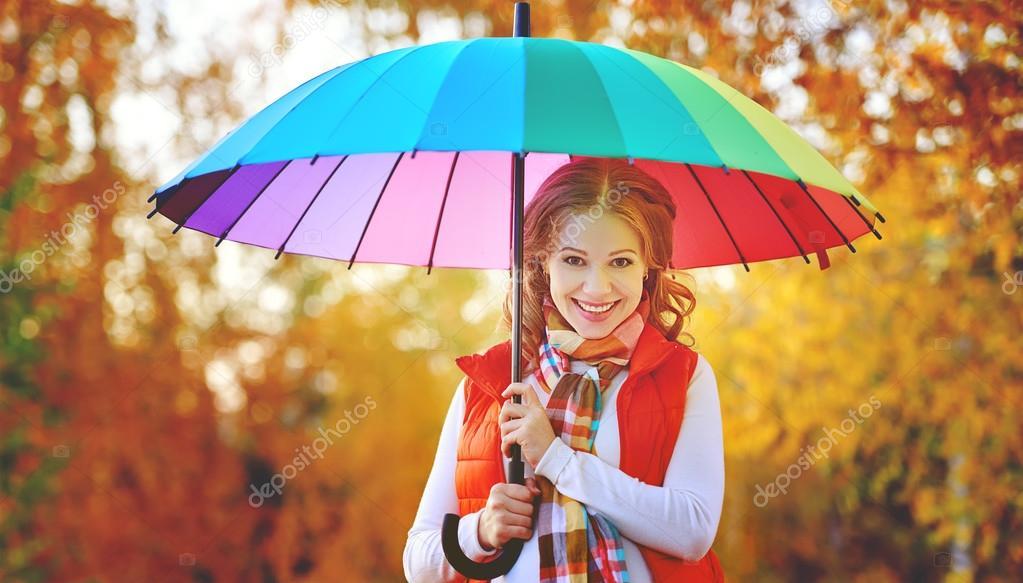 happy woman with rainbow multicolored umbrella under rain in par