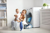 mother a housewife with a baby  fold clothes into the washing ma