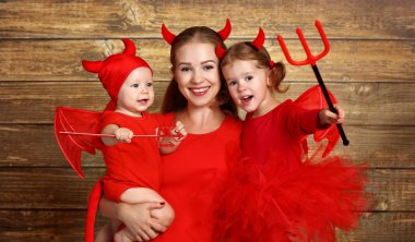 happy family with costumes devil prepares for Halloween