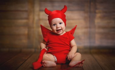 Funny baby in devil halloween costume on wooden background