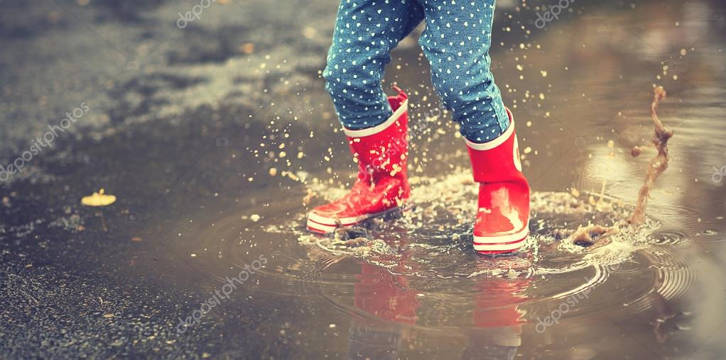 legs of child in red rubber boots jumping in autumn puddles