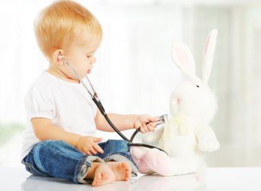Baby plays in doctor toy bunny rabbit and stethoscope