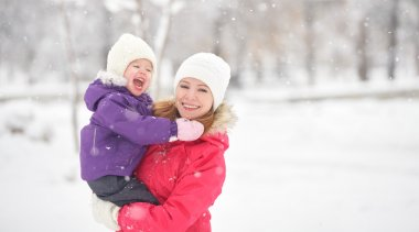 happy family mother and baby girl daughter playing and laughing in winter snow