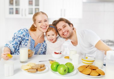 Happy family mother, father, child baby daughter having breakfast
