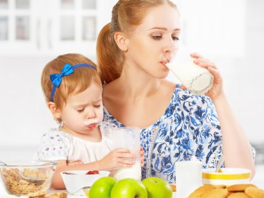 Happy family mother and baby daughter  girl at breakfast: biscuits with milk