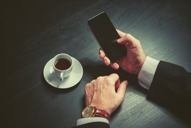 phone and a cup of coffee in the hands of a businessman in dark colors