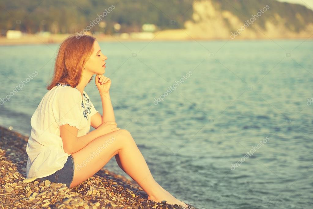 sad girl sitting on the  beach and looks into the distance at sea