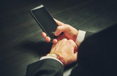 phone in hands of a businessman in dark