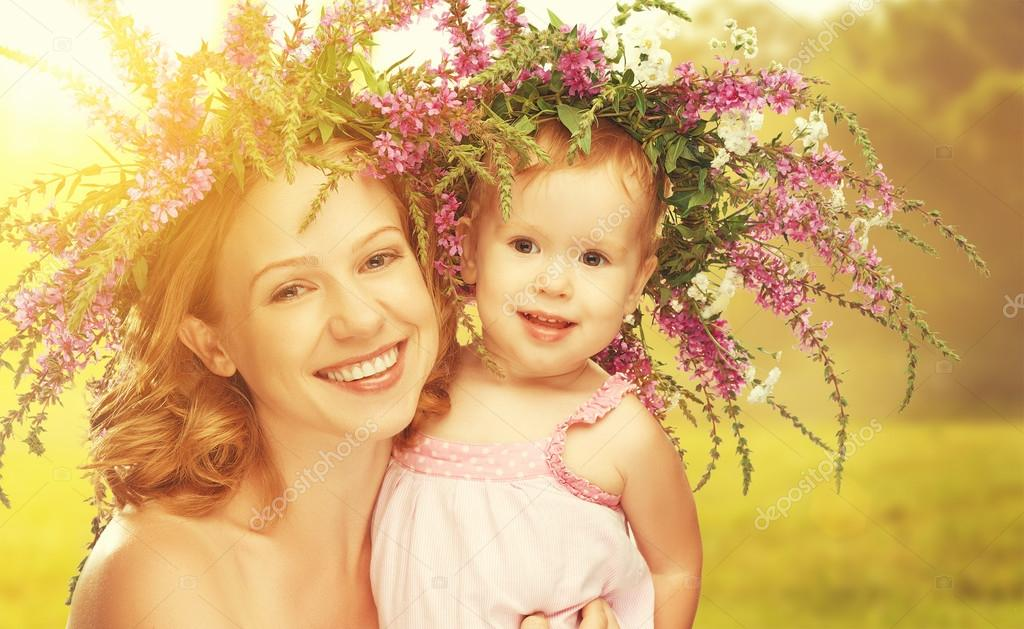 happy laughing daughter hugging mother in wreaths of summer flow