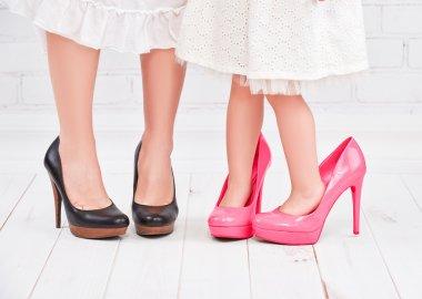 Legs mother and daughter little girl fashionista in pink shoes on high heels stock vector