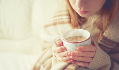 cup of hot coffee warming in the hands of a girl