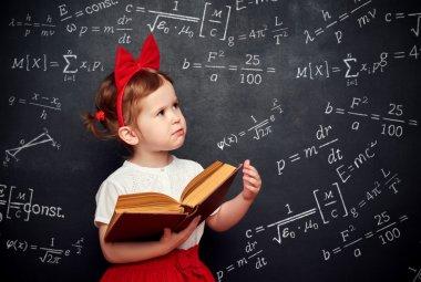 wunderkind little girl schoolgirl with a book from the blackboar
