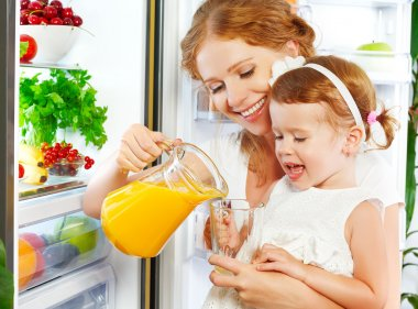 happy family mother and baby daughter drinking orange juice in