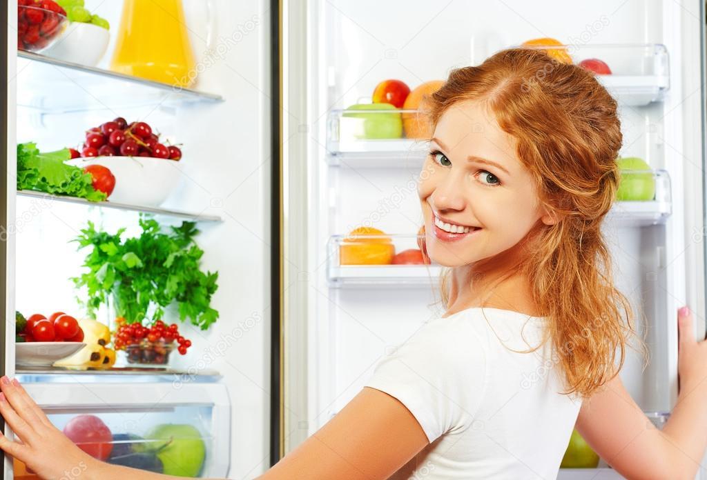 glückliche Frau und offenen Kühlschrank mit Obst, Gemüse und er ...