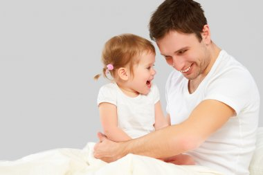 Happy family father and baby  daughter playing in bed