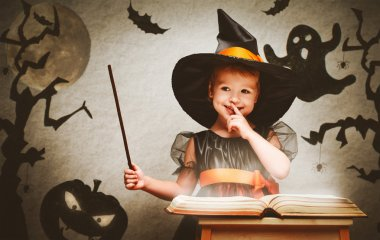 Halloween. cheerful little witch with magic wand and book conjur